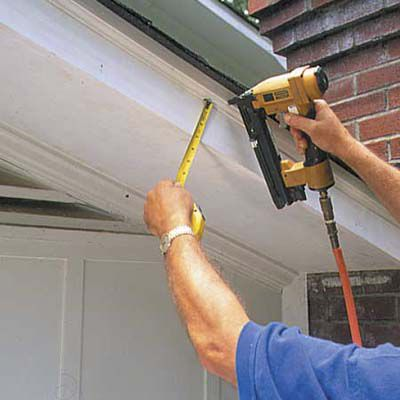 Man Attaches Shingle Mold Along Top Of Fascia Of Roof