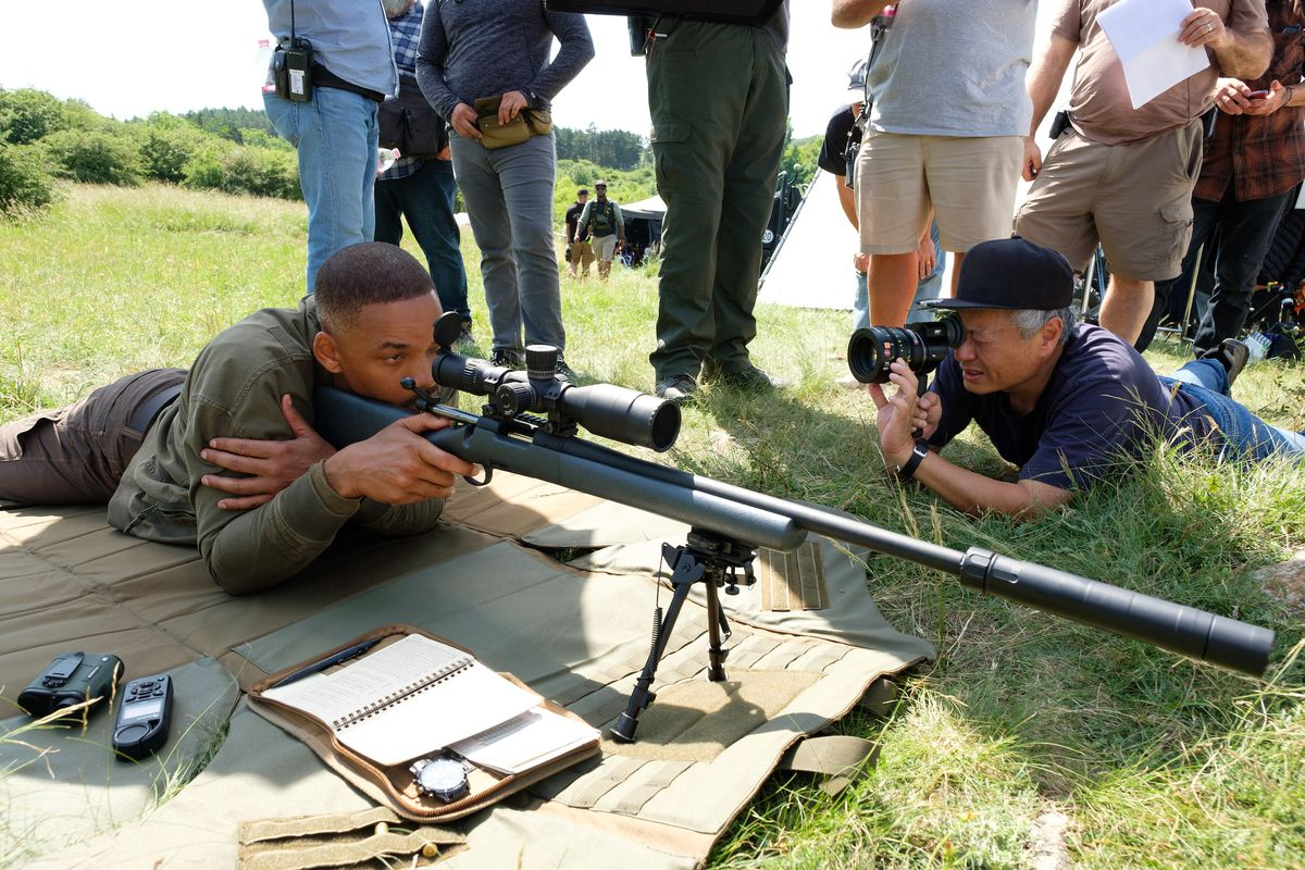 Will Smith lays on the ground aiming a sniper rifle  as director Ang Lee lines up his shot with a viewfinder