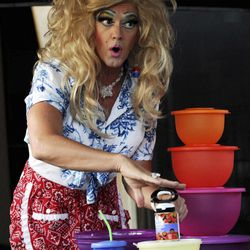 This Friday, Aug. 5, 2011 photo shows Kevin Farrell dressed as Dee W. Ieye selling Tupperware products during a Tupperware party in Bellflower, Calif. Tupperware, it seems, is enjoying a renaissance 65 years after it first hit the market with Wonder Bowls, Bell Tumblers and Ice-Tup molds for homemade frozen treats.
