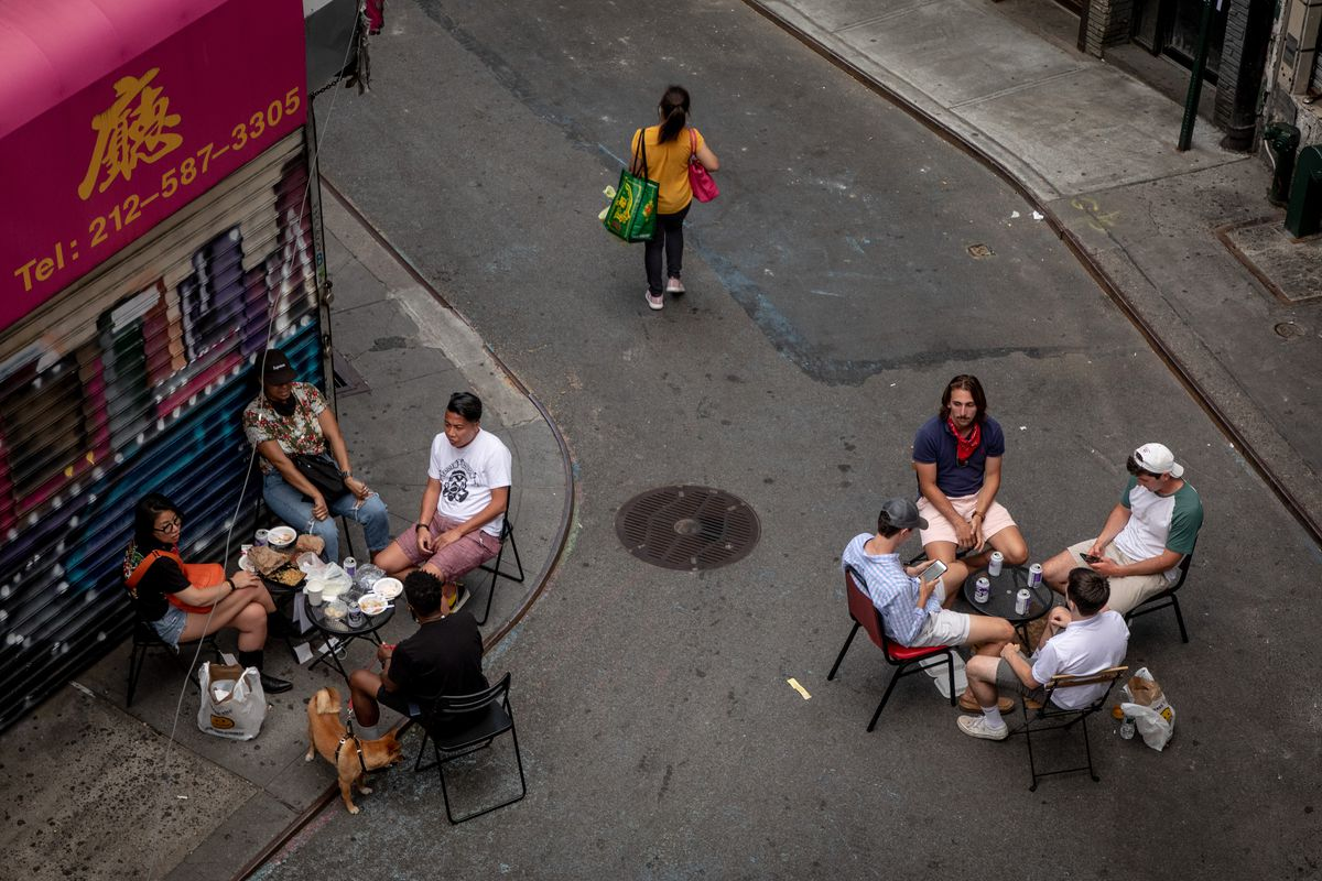 Two groups of people eat and drink while sitting at tables set up outside on the street.
