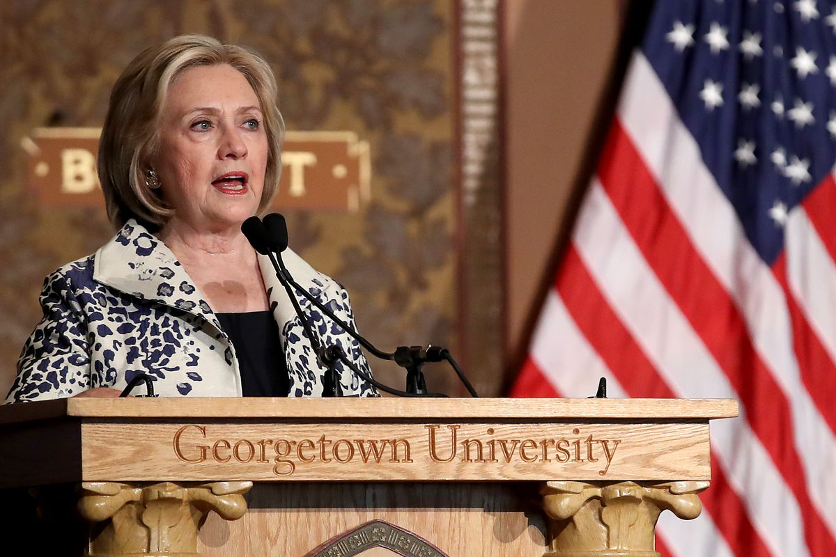 Former US Secretary of State Hillary Clinton speaking from behind a Georgetown University podium beside an American flag.