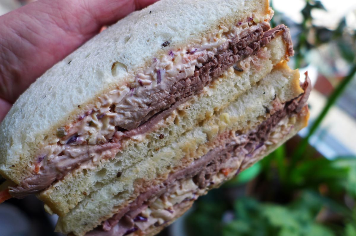A roast beef and coleslaw sandwich on rye, cut in the middle to show the layered interior