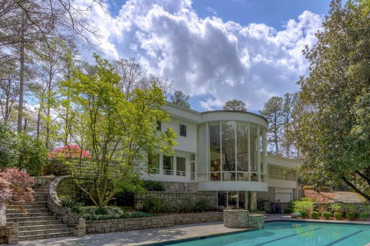 Two-story house overlooks swimming pool.