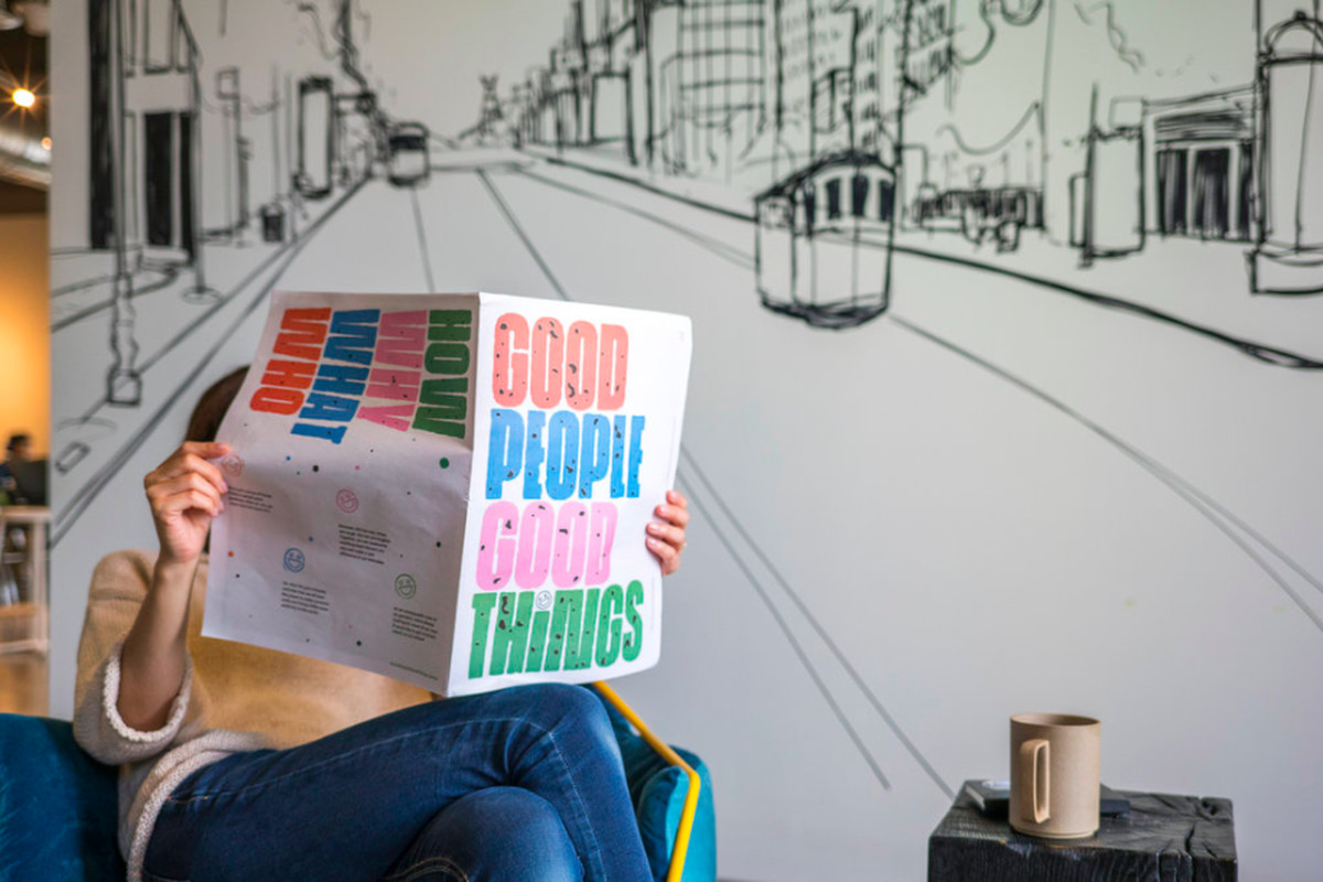 """A person sits in front of a black-and-white mural reading a paper titled """"Good People, Good Things."""""""
