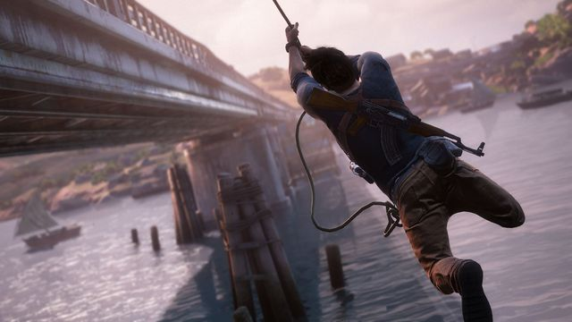 Nathan Drake swings alongside a bridge with his back to camera in Uncharted 4: A Thief's End