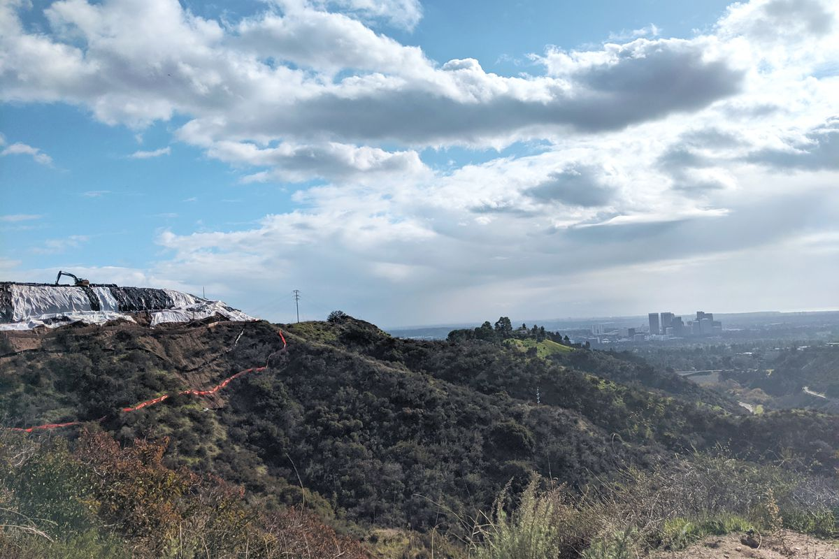 A hillside with a bunch of plastic on it and an earthmover atop it. In the backround, there is a view of the city, partly obscured by smog, and the outlines of a cluster of tall buildings.