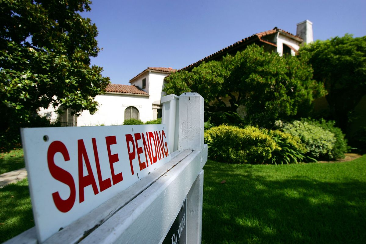 Home with sale pending sign in foreground