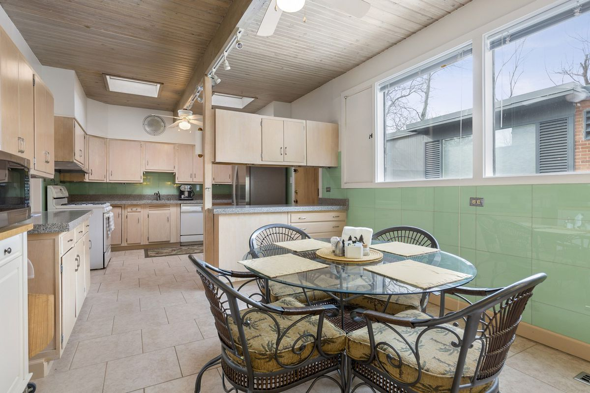A circular table with four chairs in a kitchen with wood cabinets and a green tile backspalsh.