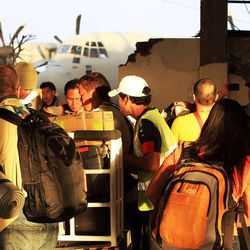 People gather their own luggage after arriving at the Tacloban airport, Thursday, Nov. 21, 2013.