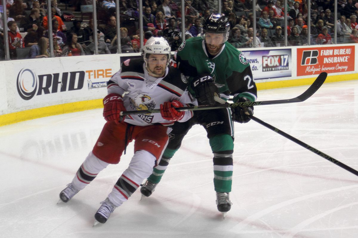 Xavier Ouellet and Derek Hulak chase the puck in a game at Van Andel Arena on Decempber 19, 2015