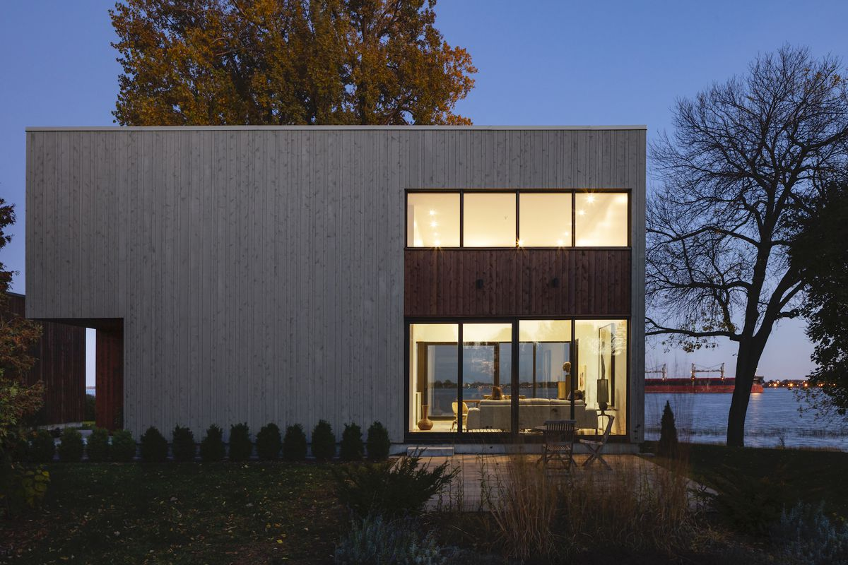 A rectangular house with large glass wall that offers view out to lake in the back.