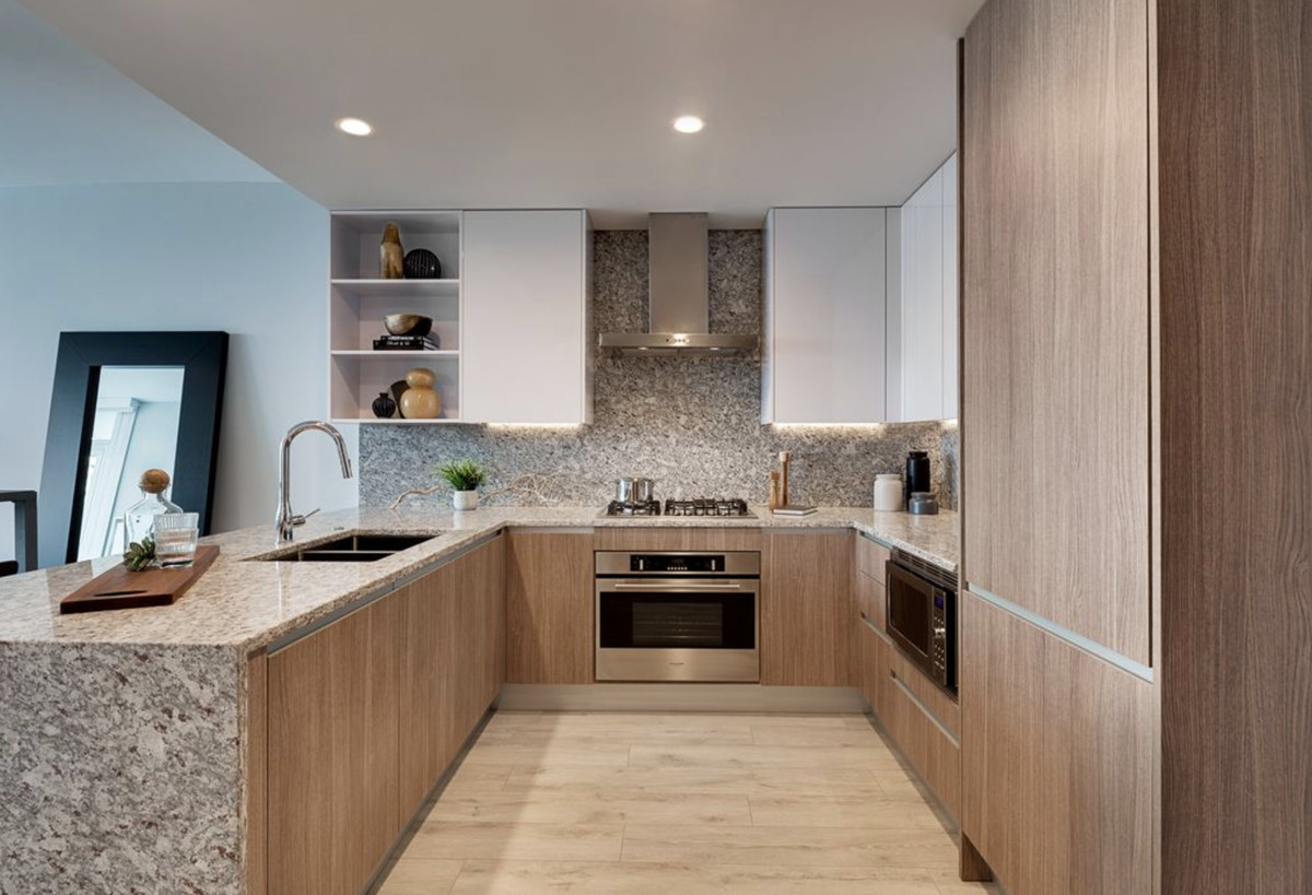 A kitchen with wood cabinets, a granite countertop, and open shelving.