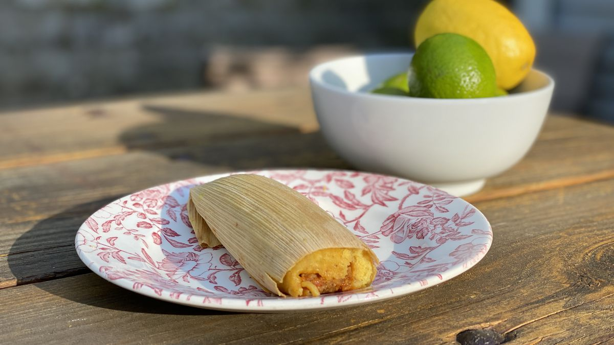 An Alpha Tamale sits on a patterned red and white plate on an outdoor picnic table