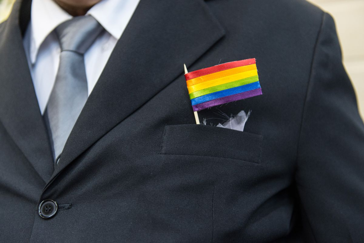 A father of a bride wears an LGBT flag during a same-sex wedding.