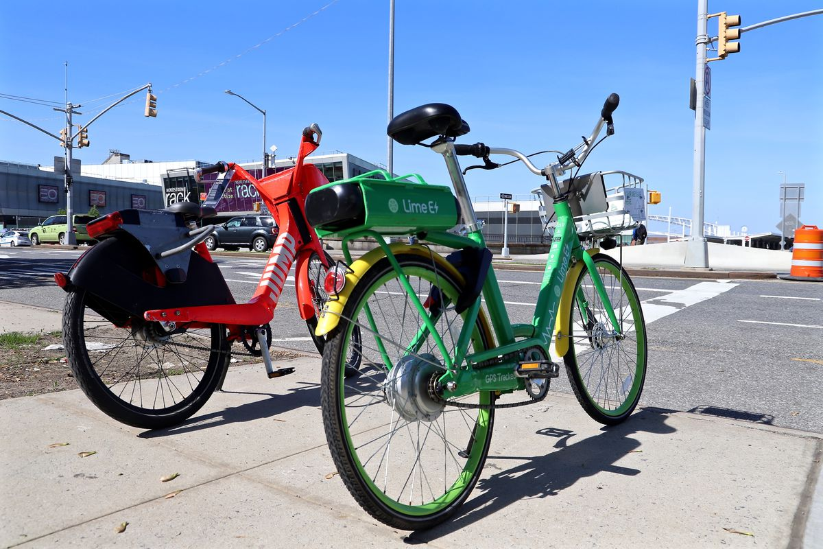 Two bikes, one red one and one green one parked on a sidewalk in Staten Island.
