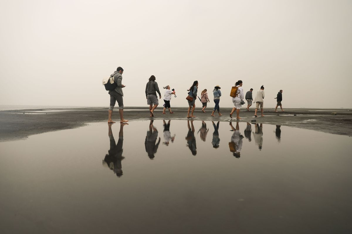 Visitors to Silver Sand Beach at Great Salt Lake Marina are reflected on still water as they walk around during a rainstorm on Wednesday, Aug. 18, 2021.