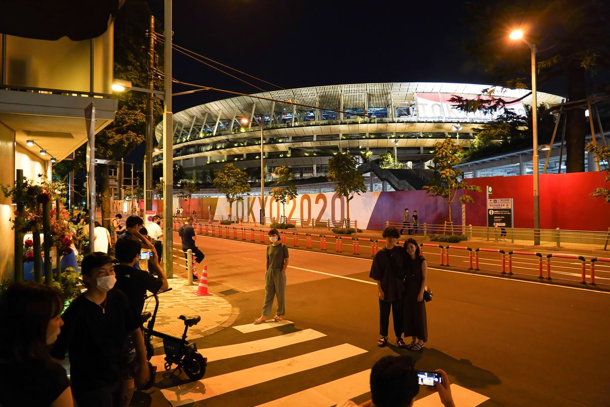 People gather and take photos outside Tokyo Olympic Stadium on the eve of the opening ceremony. With just one day until the Olympics opening ceremony, Tokyo confirms 1,979 new coronavirus infections. The total number of cases in Tokyo now stands at 195,041.
