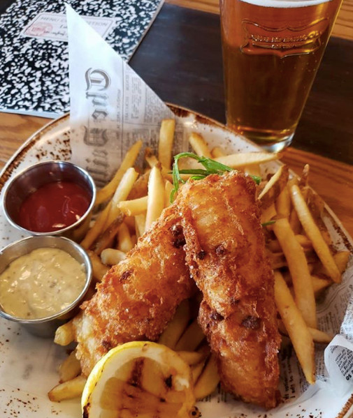 Fish and chips with a beer in the background
