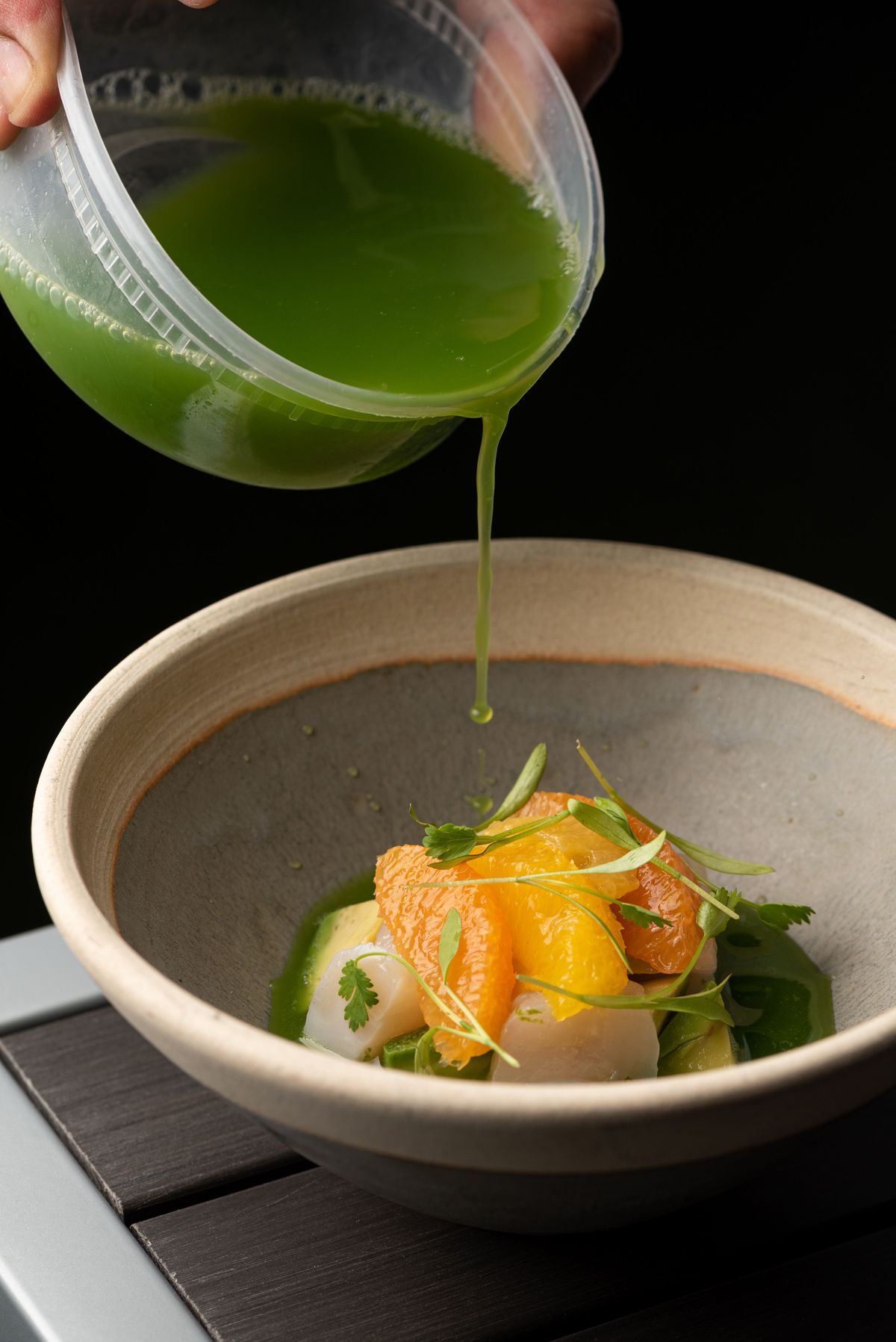 A crudo with citrus on top and a splash of green liquid poured in.