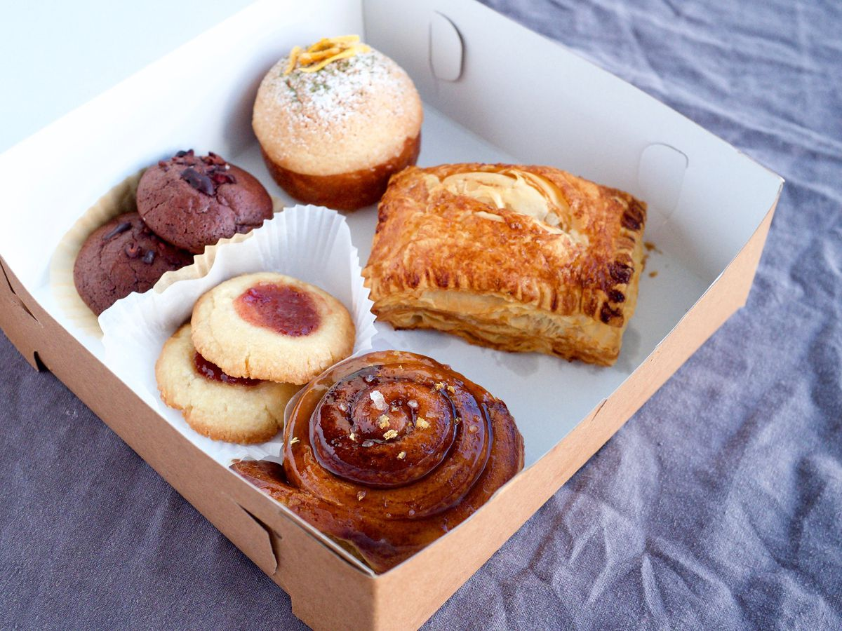 A paper box sitting open to reveal a variety of baked treats and cookies
