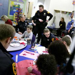Salt Lake City police officers play with patients and their family members at Primary Children's Medical Center in Salt Lake City on Thursday, Jan. 19, 2012.