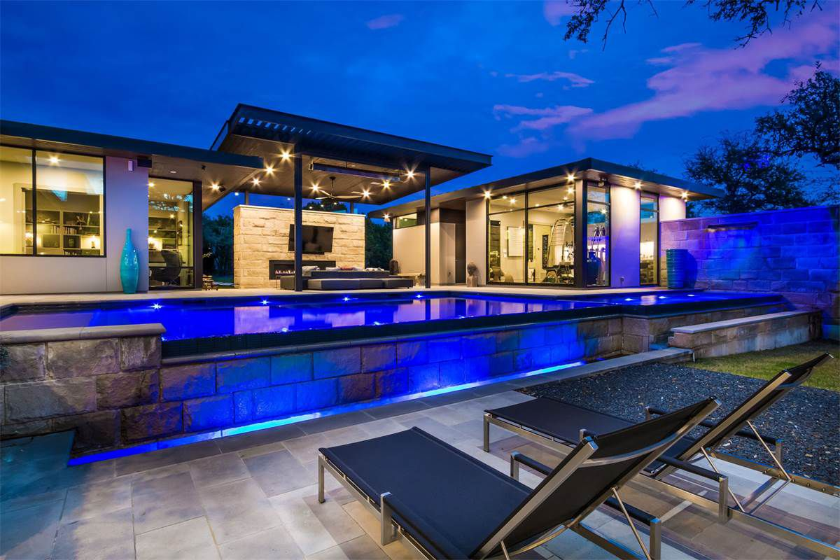 Contemporary home at dusk, pool out front