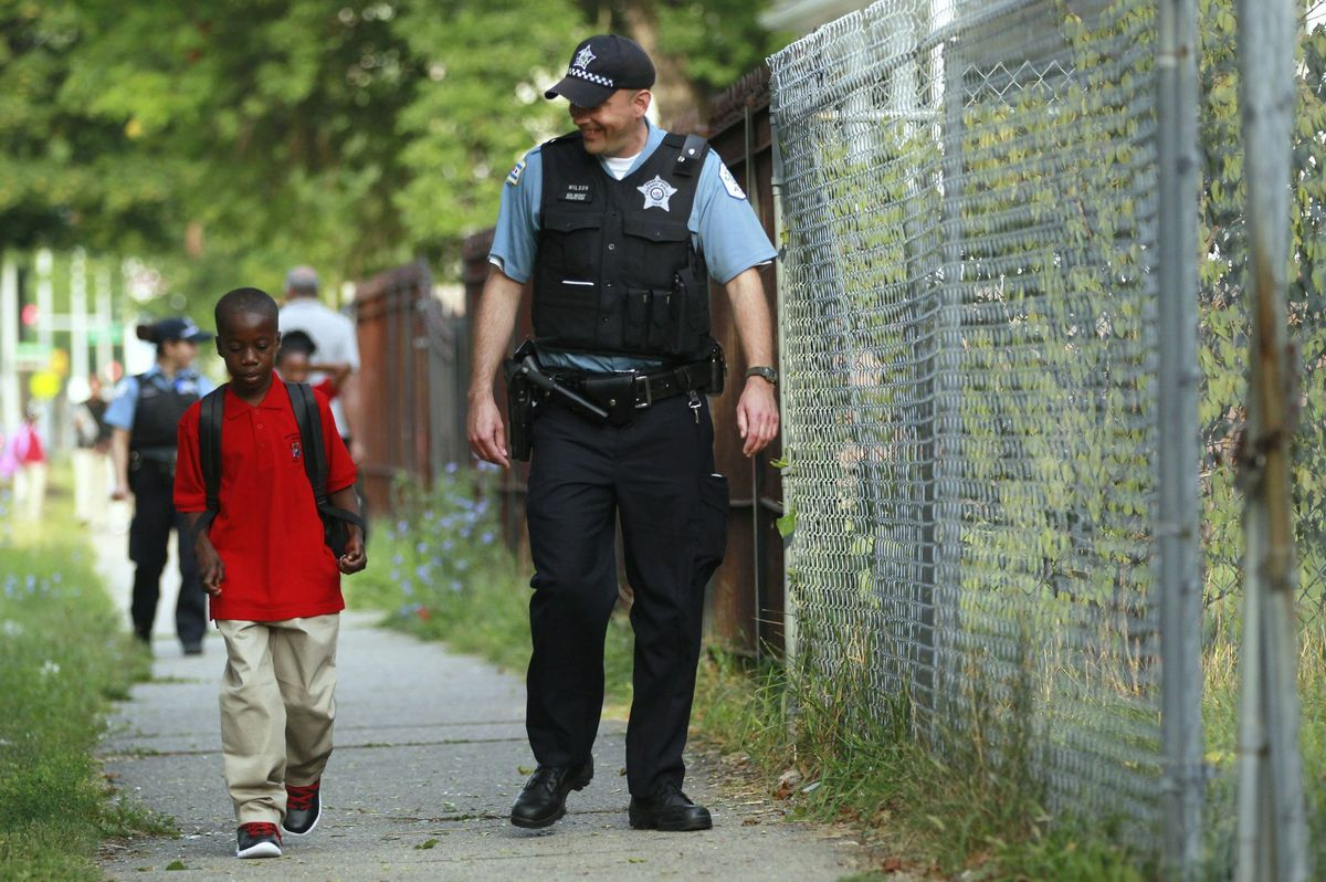 A police officer walks with a student.
