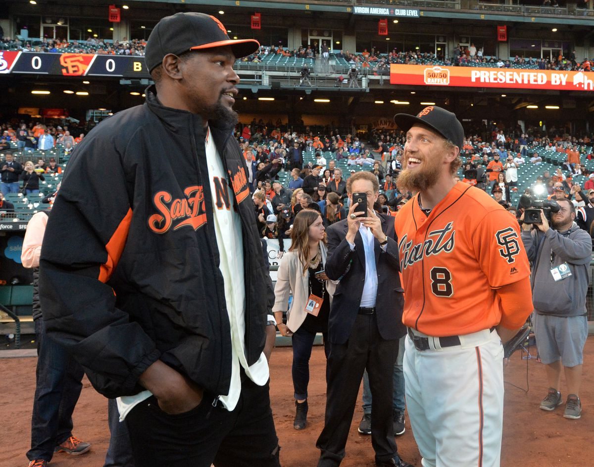 Before throwing out the ceremonial first pitch, Golden State Warriors player Kevin Durant, left, talks with San Francisco Giants outfielder Hunter Pence (8) before the start of the Giants baseball game against the St. Louis Cardinals in San Francisco, Cal