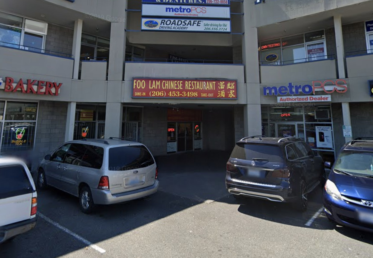 The exterior of Foo Lam Chinese Restaurant, located in a South Seattle strip mall packed with cars in parking spots
