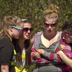 From left, Emily Ferree, 20, Sara Paullin, 19, Amber Boyce, 19, and Mia Graves, 18, friends of two women who perished in a house fire in North Bend, Wash. Sunday, April 22, 2012, grieve upon arriving near their home. The four girls were very close friends with the victims, and are recent high school graduates of the class of 2011. Detectives are investigating their deaths as a double homicide.