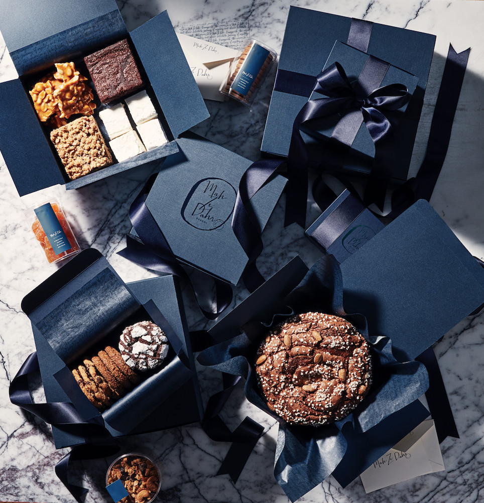 Black or dark blue boxes with wide black ribbons, with some open to show pastries, brownies, and cookies.
