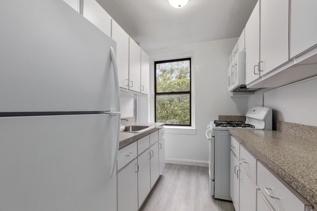 A kitchen with white cabinetry, hardwood floors, and a window.