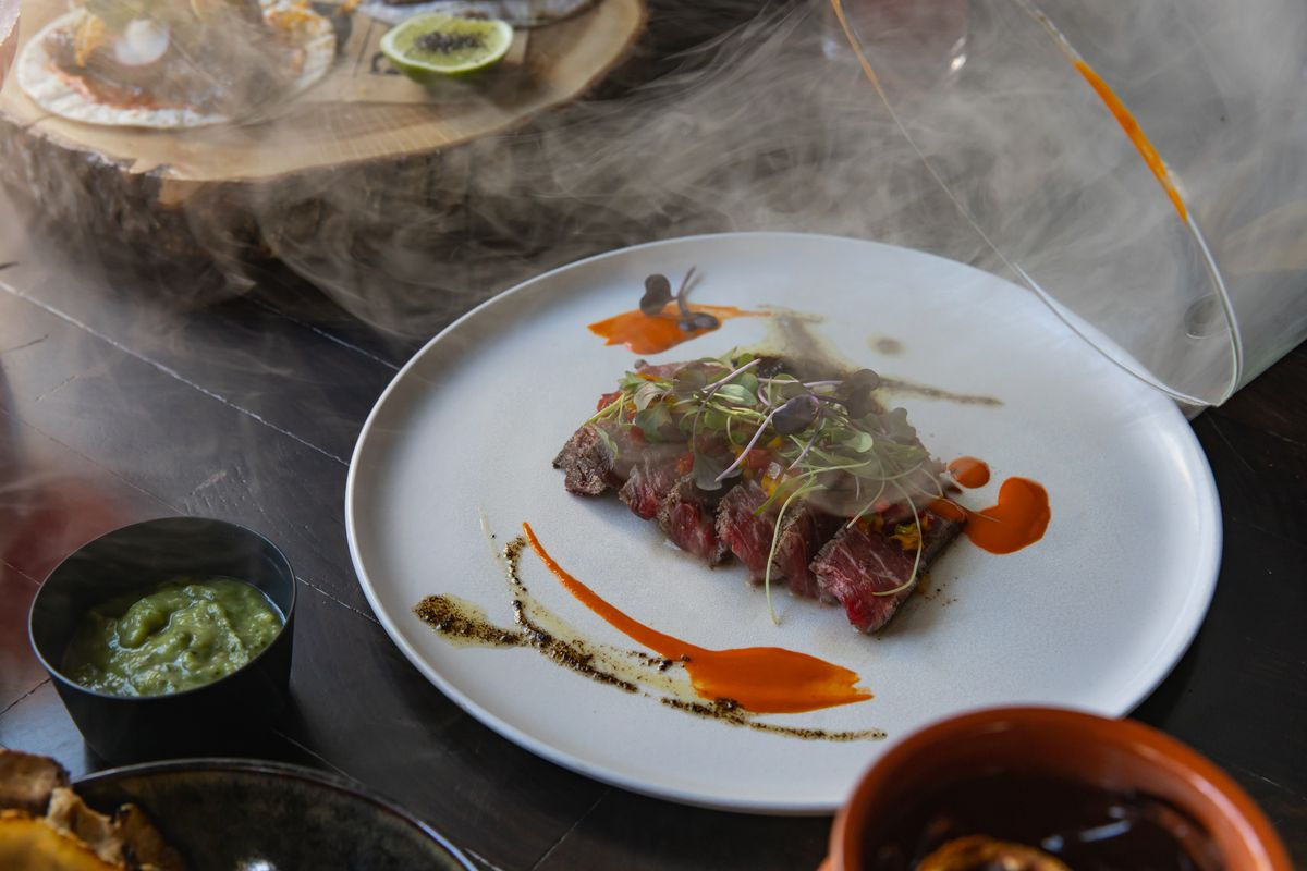 Wagyu steak a la piedra arrives in a smoking chamber