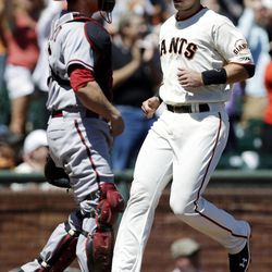 San Francisco Giants' Buster Posey, right, scores on a triple by Hunter Pence against the Arizona Diamondbacks during the first inning of a baseball game, Monday, Sept. 3, 2012, in San Francisco.