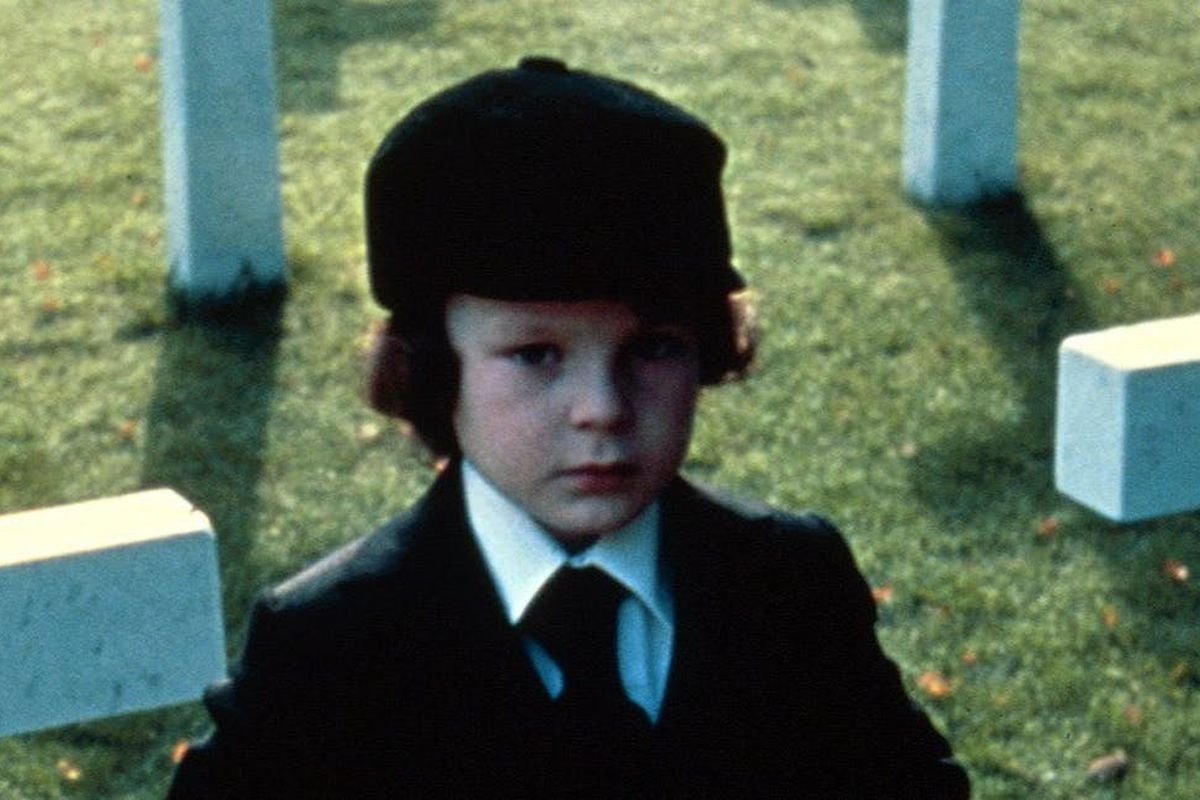 Still of a young boy standing in a cemetery in a horror movie