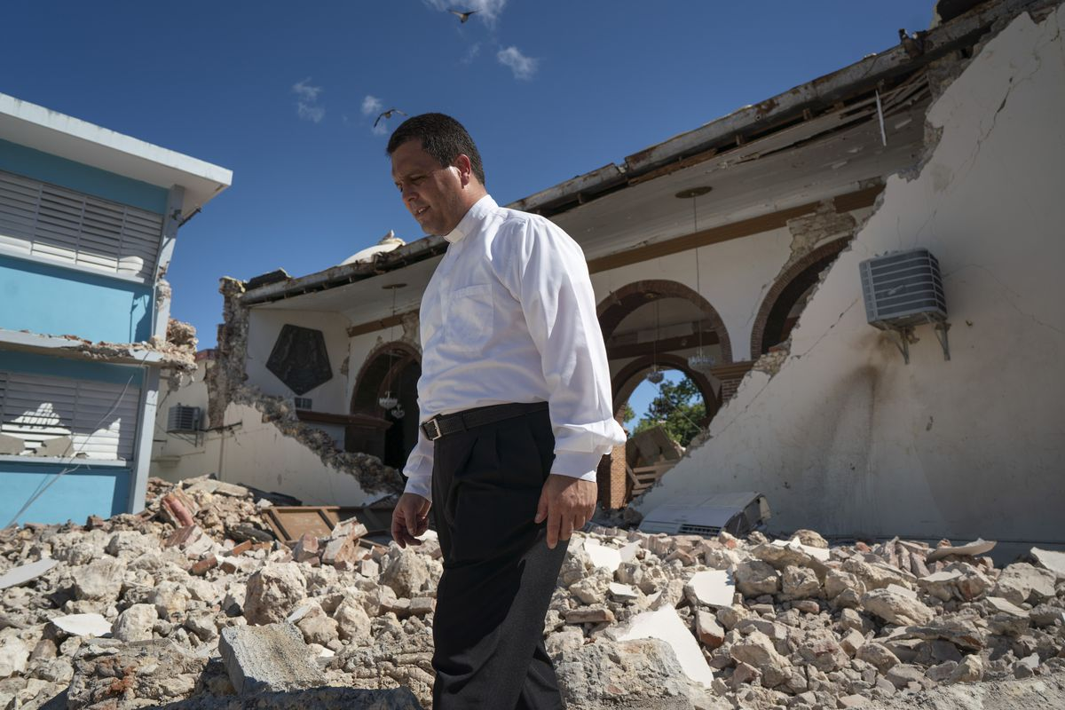 Aponte walks amid rubble, his head bowed; the inside of his church is clearly visible, its arches and pews now out in the open.