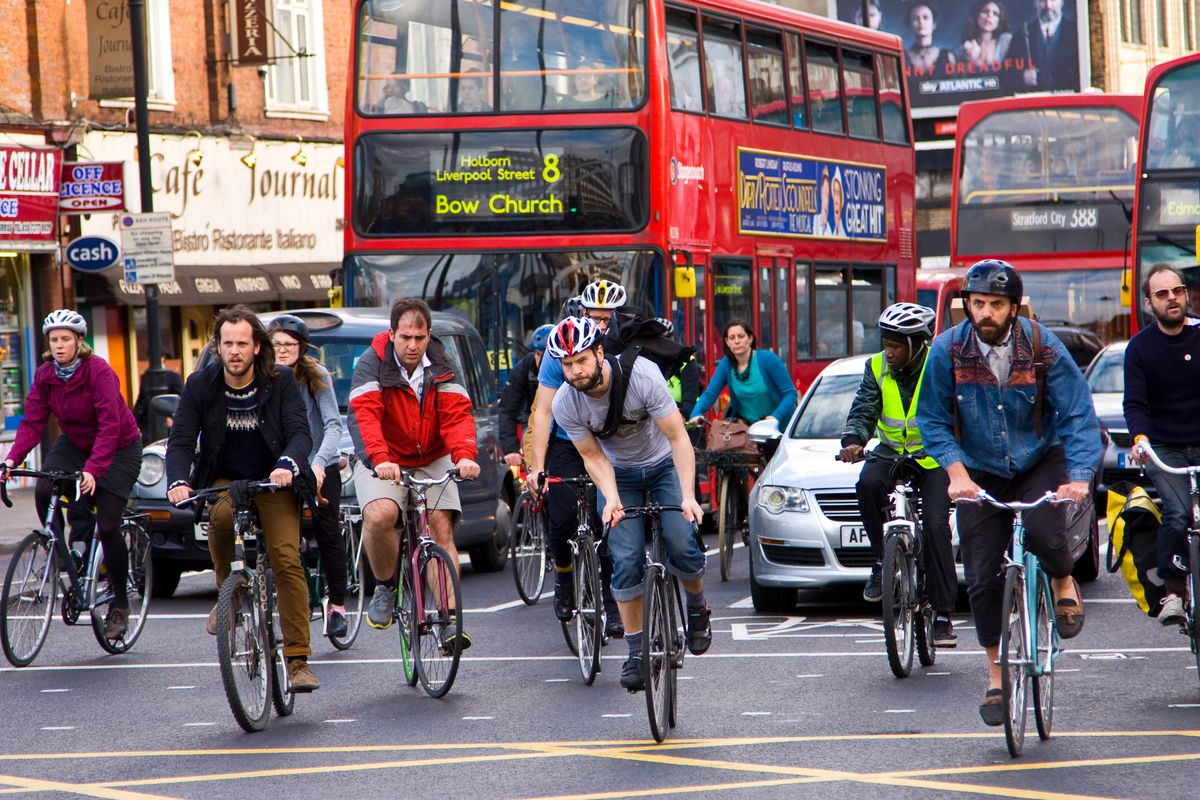 Cyclists, car, and buses on a London street.