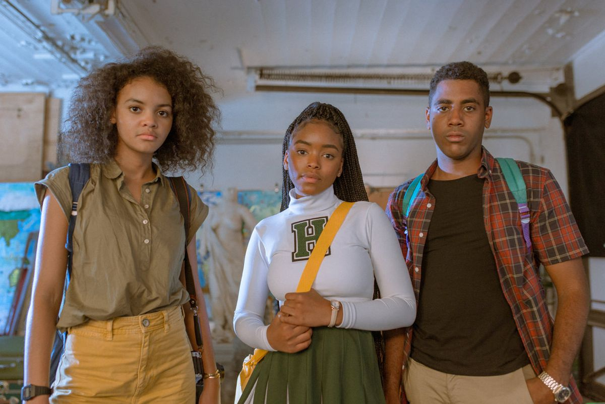 Three teenagers stand together, looking straight at the camera.