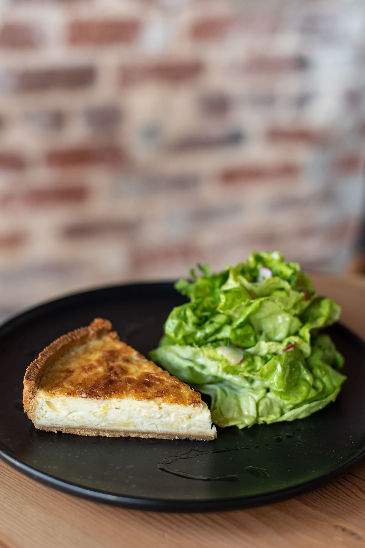 A triangle of a quiche with leeks and a side salad.