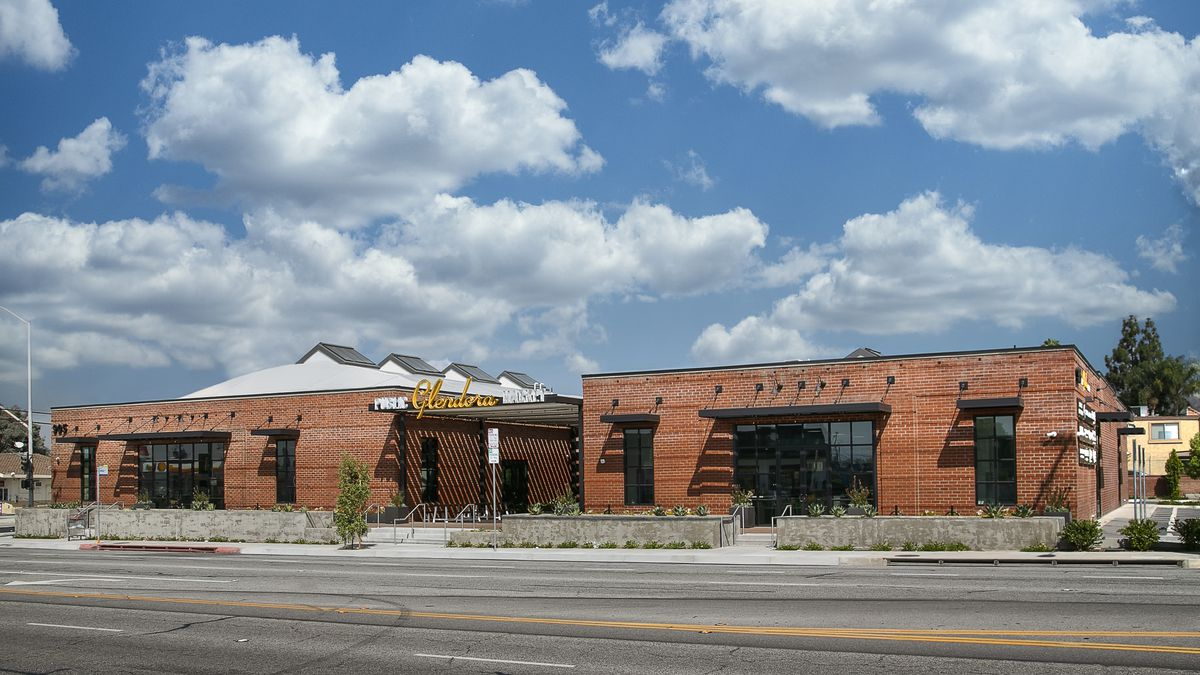 A long-lens exterior shot of a food hall that uses a converted brick building.