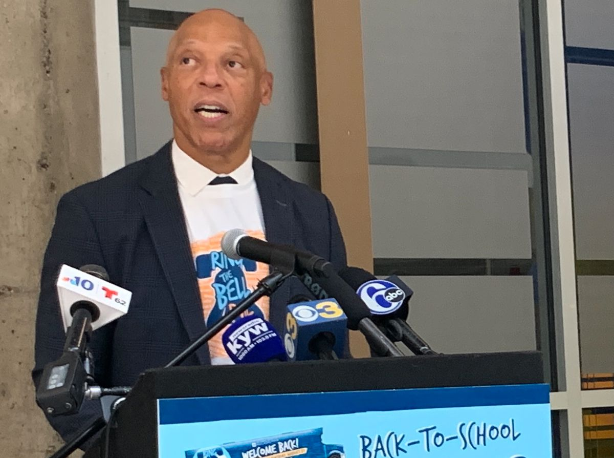 """Superintendent William Hite speaks into microphones at a podium that, in part, reads """"back-to-school""""."""