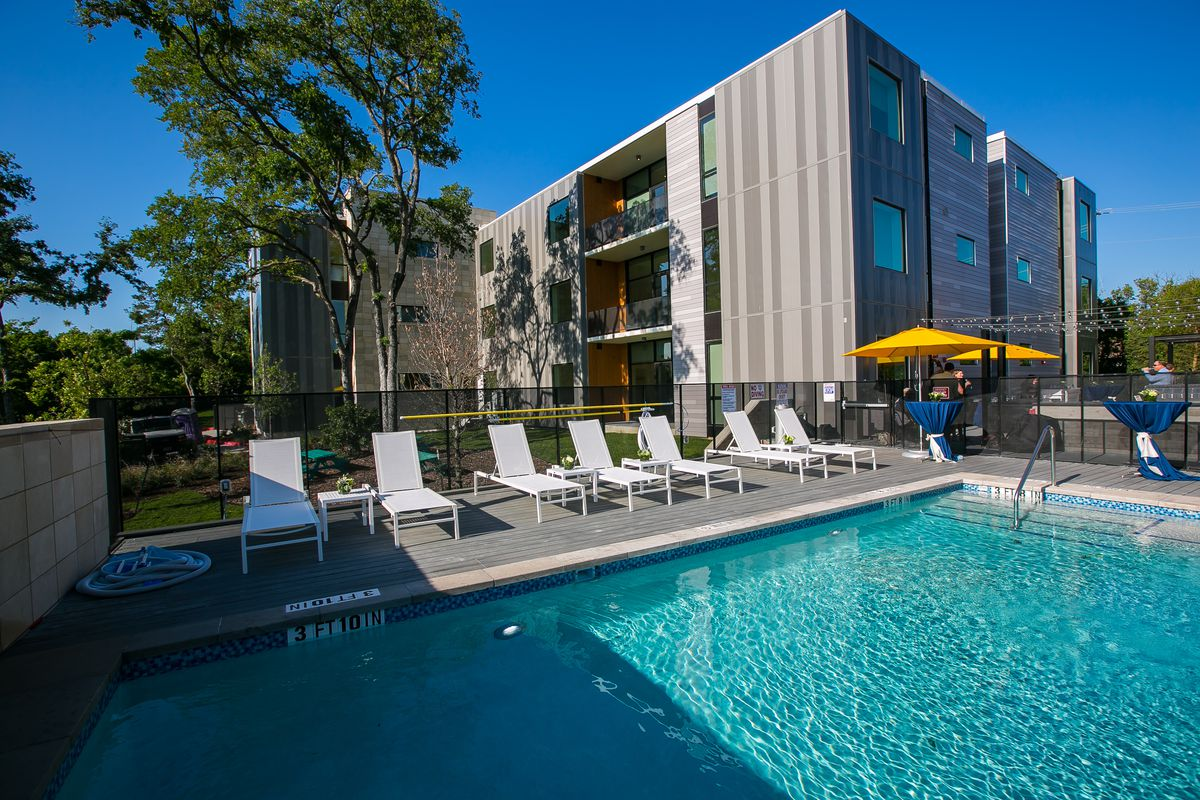 Three-story, metal-clad apartment building with pool in front