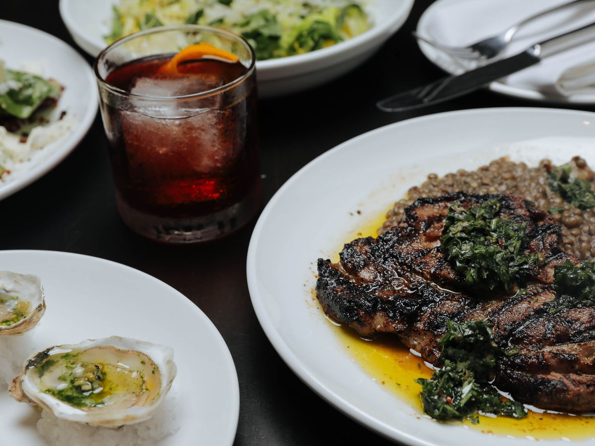 An assortment of dishes are placed on a dark wood table, including a steak bathing in oil, oysters, and what appears to be a Negroni