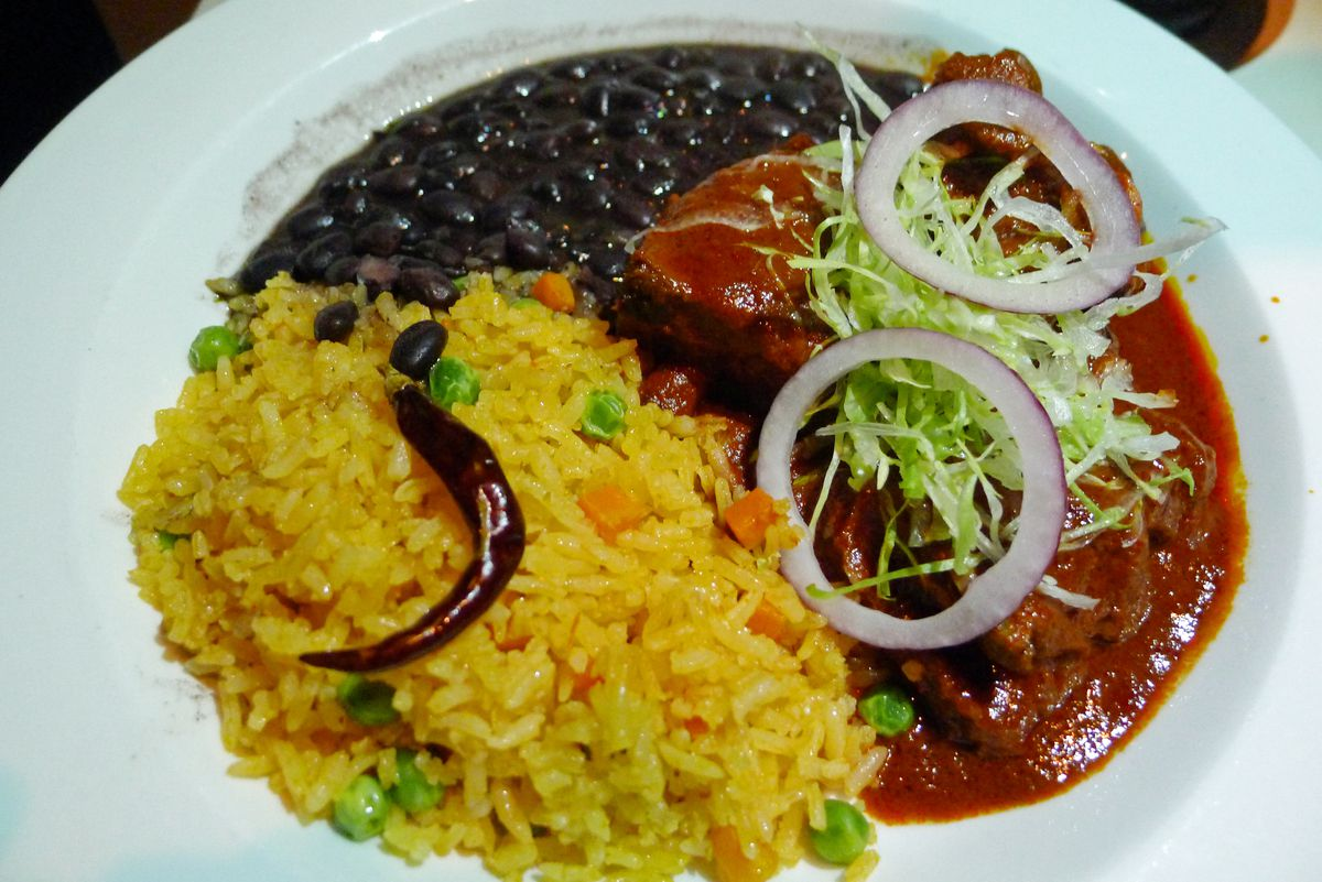 Black beans, yellow rice, and some bright red pork ribs in thick sauce.
