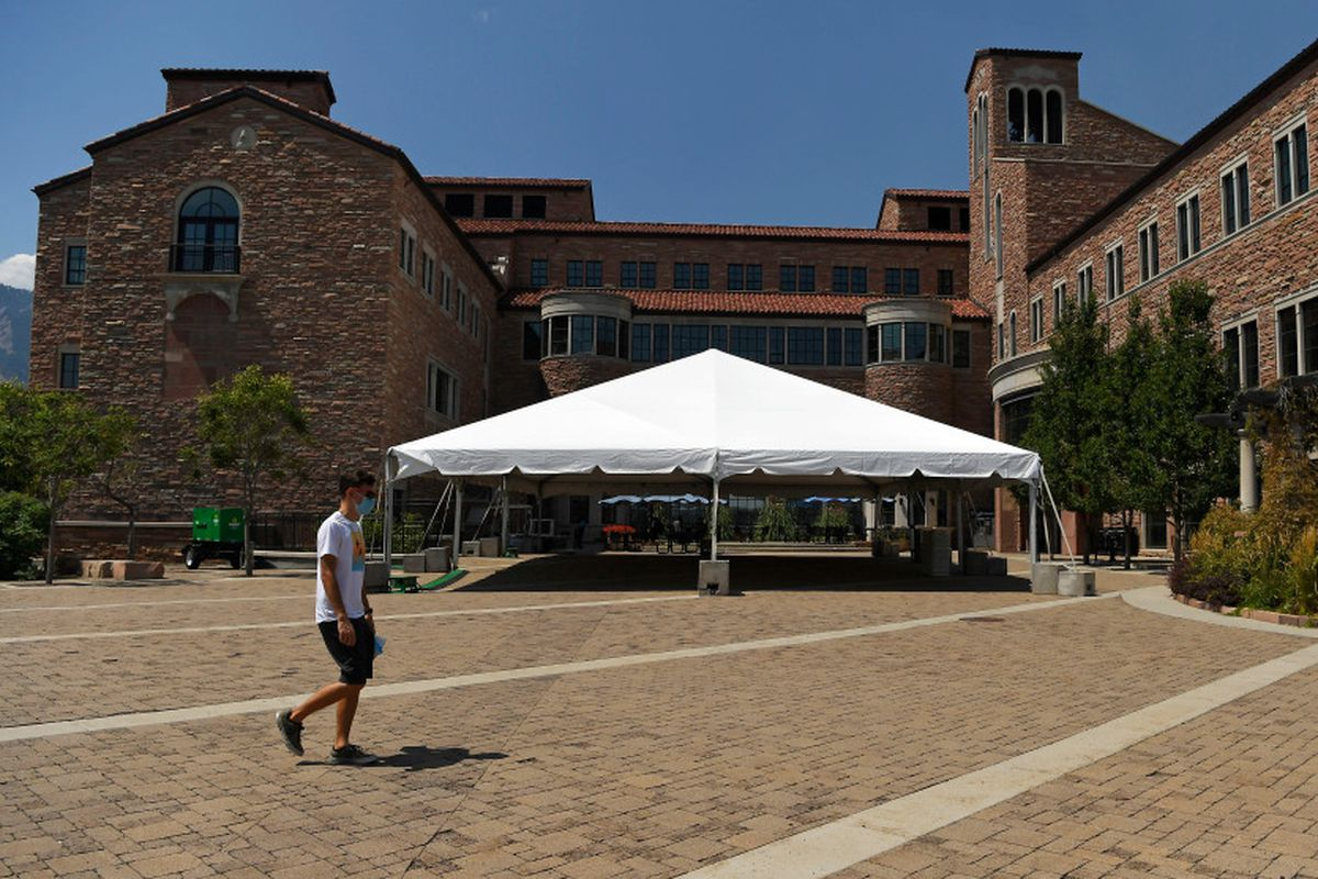 Young man walks across plaza outside the center for community complex at University of Colorado Boulder.