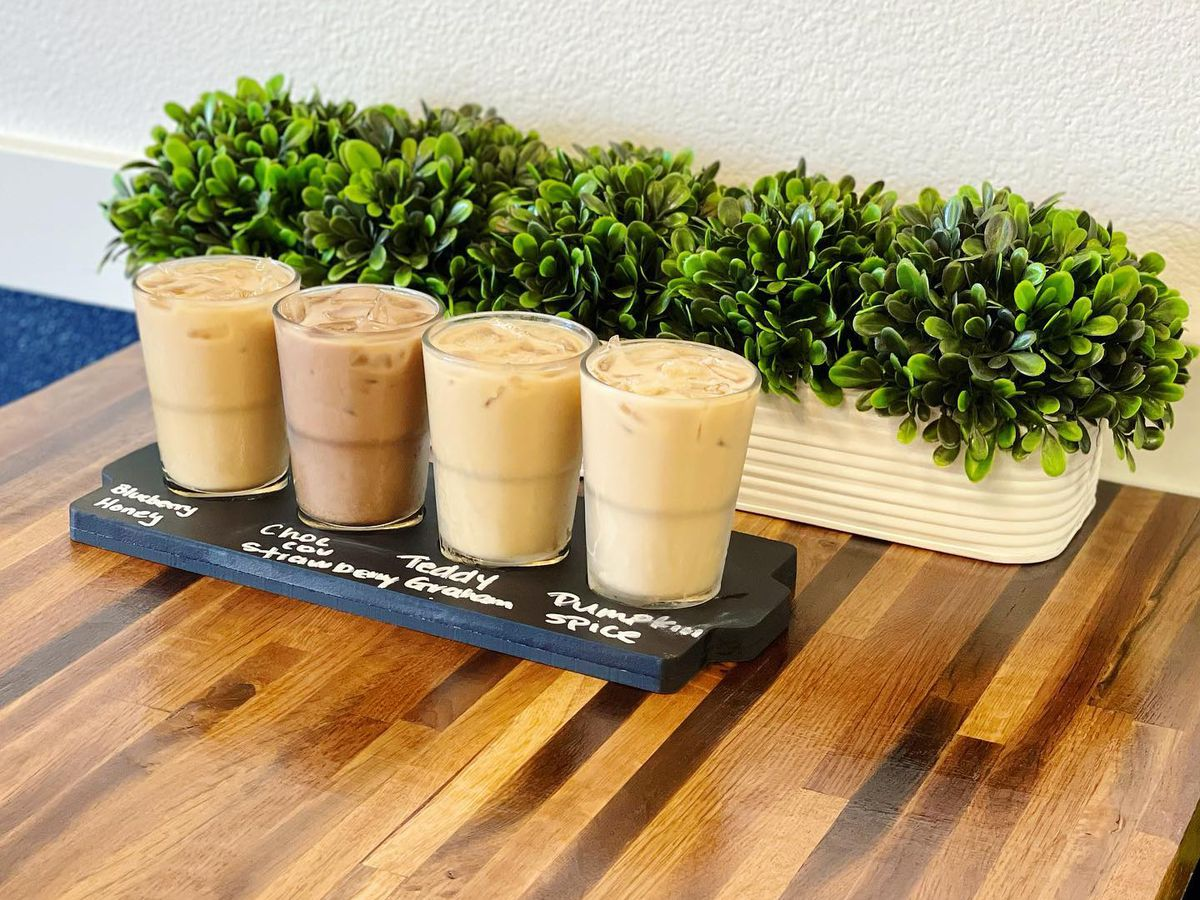 Four small coffees in clear glasses on a wooden table with a small plant behind.