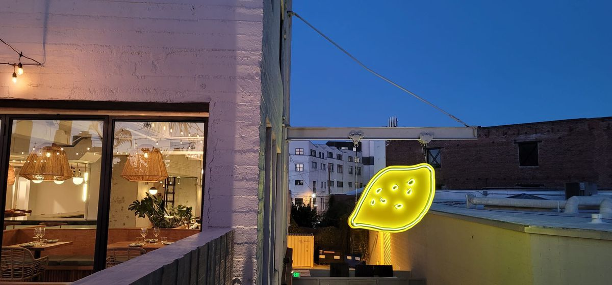 A semi-hidden view into a rooftop bar and restaurant with a glowing lemon sign.