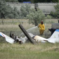 A South Davis Metro firefighter works at the scene of plane crash that started a brush fire near Legacy Parkway in Centerville on Thursday, June 25, 2020. Bystanders who were traveling on Legacy Parkway pulled two people from the burning plane, who were then transported to the hospital with serious injuries.