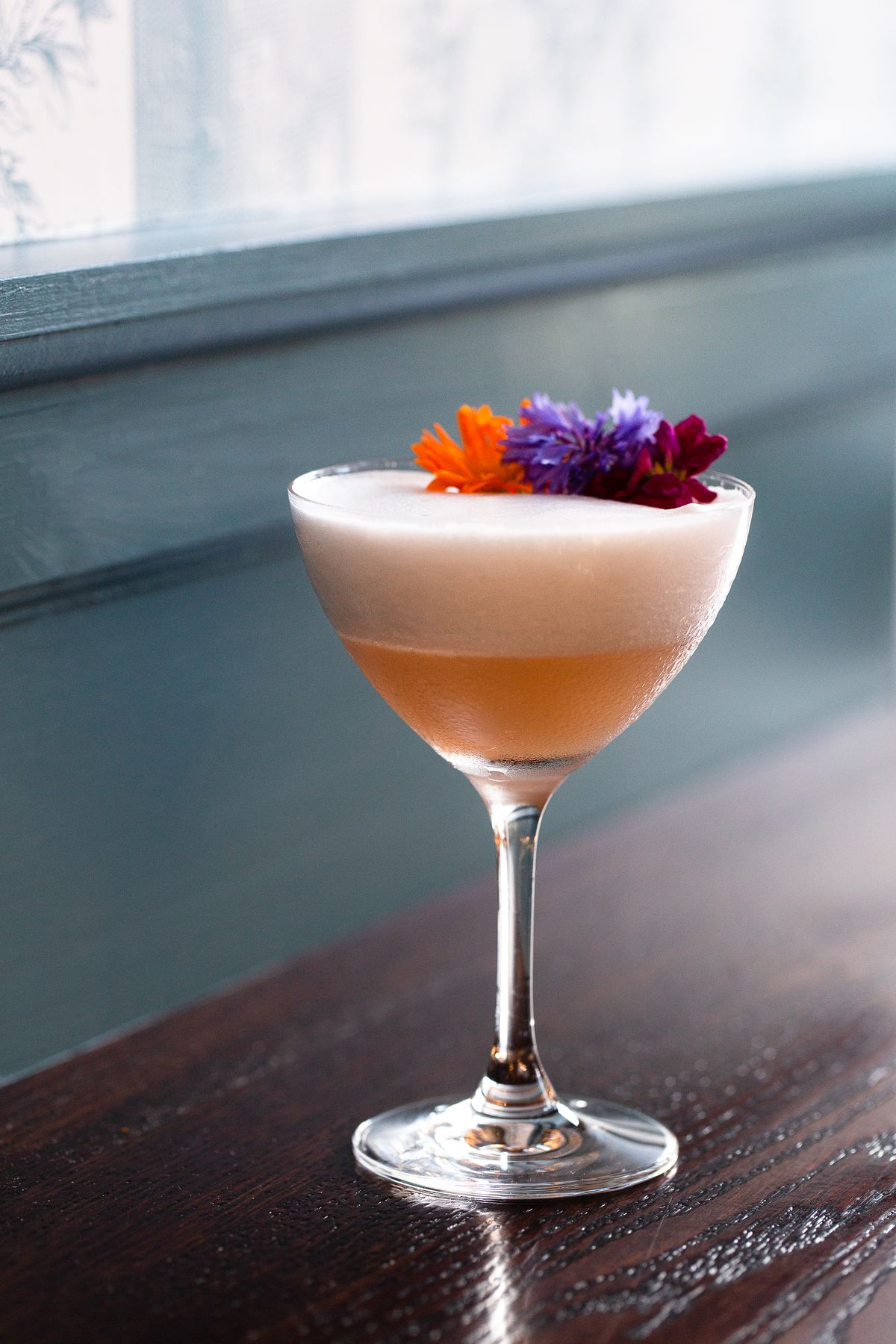 Closeup shot of a pink cocktail with a foamy top, garnished with pink and purple flowers