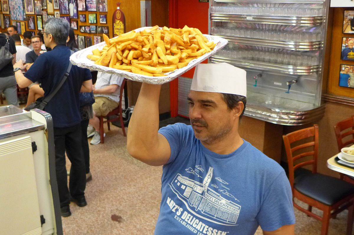An smiling employee in a blue Katz's tee shirt holds a tray of steak fries aloft...